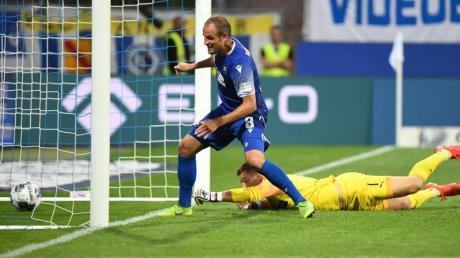 Der Karlsruher Manuel Stiefler (l) erzielt den Treffer zum 1:0 gegen Sandhausens Torwart Martin Fraisl. Foto:Uli Deck