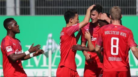 Kiels Torschütze Janni-Luca Serra (M) jubelt mit seinen Teamkollegen über das 1:0 im Spiel gegen Fürth.