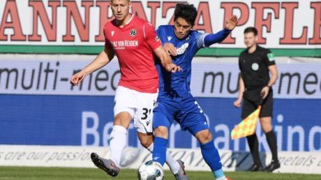 Der Karlsruher Kyoung-rok Choi (r) versucht den Hannoveraner Waldemar Anton vom Ball zu trennen. Foto: Uli Deck/dpa