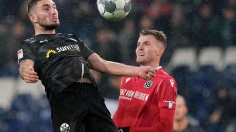 Sandhausens Marlon Frey (l) kommt vor Marvin Ducksch von Hannover 96 an den Ball. Foto: Peter Steffen/dpa