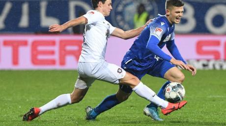 Der Karlsruher Marvin Wanitzek (l) und der Auer Clemens Fandrich kämpfen um den Ball. Foto: Uli Deck/dpa