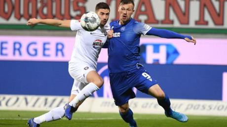 Der Karlsruher Marvin Pourie (r) und der Auer Marko Mihojevic kämpfen um den Ball. Foto: Uli Deck/dpa