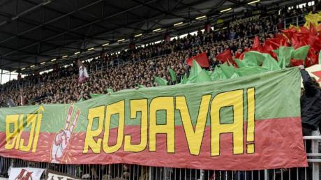 Fans von St. Pauli halten ein prokurdisches Banner mit dem Schriftzug «Biji Rojava» («Es lebe Rojava») in die Höhe.