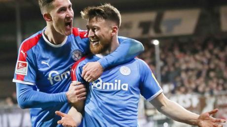 Holstein Kiels Salih Özcan (r) und Phil Neumann feiern Özcans Tor zum 1:0 gegen den FC St. Pauli.