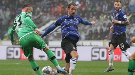 Die Spieler von Arminia Bielefeld und Hannover 96 kämpfen in der Schüco-Arena auf durchweichtem Rasen um den Ball.