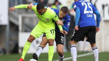 Bielefelds Cedric Brunner (M) und Jonathan Clauss (r) bedrängen im Kampf um den Ball mit Daniel-Kofi Kyereh (l) aus Wiesbaden.