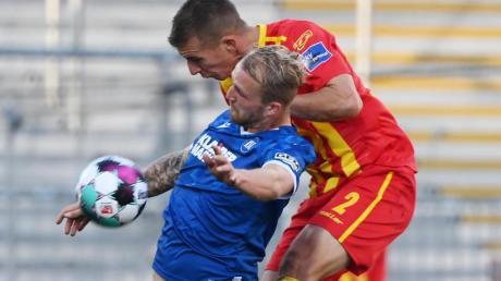 Der Karlsruher Philipp Hofmann (l) und Uwe Hünemeier vom KSC kämpfen um den Ball.