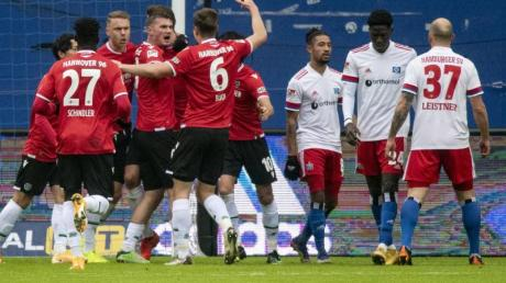 Hannovers Spieler feiern den Treffer zur 1:0-Führung, während die Hamburger (r) damit hadern.