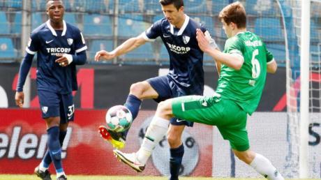 Bochums Anthony Losilla (M) und Hannovers Jaka Bijol (r) kämpfen um den Ball, links sieht Bochums Armel Bella-Kotchap zu.