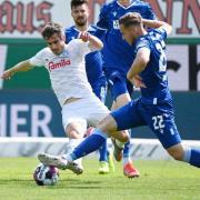 Karlsruhes Christoph Kobald (r) kämpft mit dem Kieler Fin Bartels um den Ball.