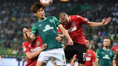 Werders Yuya Osaka (l) köpft den Ball vor Hannovers Marvin Ducksch weg.
