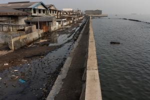 Die Schutzmauer hilft nur vorübergehend: Leere Gebäude stehen entlang eines Ufers in Muara Baru, North Jakarta, Indonesien. Das Gebiet liegt unter dem Meeresspiegel und ist häufig von Überschwemmungen betroffen.