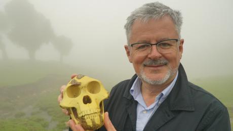 """Historiker Christopher Clark zeigt einen Schädel der menschlichen Vorfahrin """"Lucy"""" in einer Szene der neuen ZDF-Reihe """"Welten-Saga""""."""