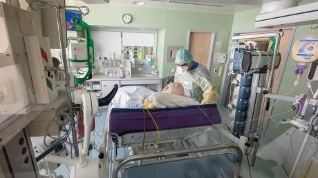 Ein Chefarzt untersucht inSchutzkleidung in einem isoliertem Intensivbett-Zimmer einen positiv getesteten Corona-Patienten.