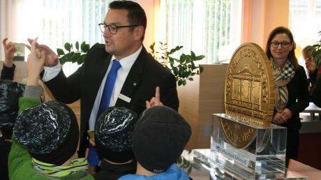 Michael Jakob, Geschäftsstellenleiter der Raiffeisenbank Hollenbach zeigt den interessierten Grundschulkindern die Goldmünze und den Goldbarren.