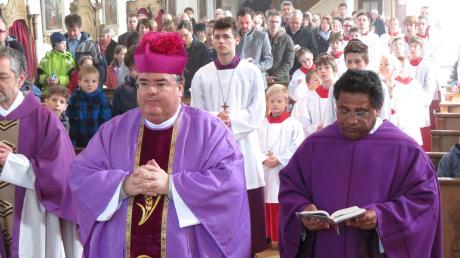 Die Geistlichkeit, (von links) Pfarrer Rudolf, Generalvikar Harald Heinrich und Pater Thomas sowie die Ministranten kurz vor dem Auszug aus der Pfarrkirche, hinter ihnen die Gottesdienstbesucher.