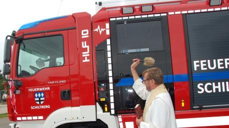 Pfarrherr Pater Markus Szymula gibt dem neuen Auto den kirchlichen Segen.