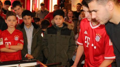 Fußball-Profi Lucas Hernández vom FC Bayern hat den Adelzhausener Bayern-Fanclub besucht. Er wurde mit Musik und Schüssen empfangen. Die Mitglieder stellten ihm Fragen und er spielte Kicker mit Kindern.