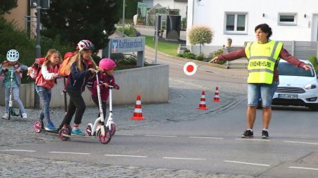 Zur sicheren Überquerung der Kreisstraße zwischen Raiffeisenbank und Rathaus im Rehlinger Ortszentrum sind Schulweghelfer im Einsatz.
