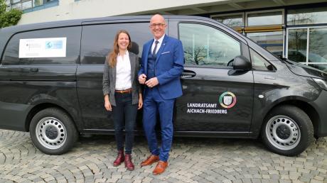 Über das neue E-Fahrzeug freuen sich Johanna Rügamer (links), Regionale Klimaschutzmanagerin, und Landrat Klaus Metzger.