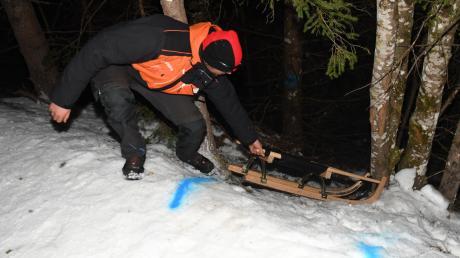 Ein Helfer zieht den Schlitten nach oben, mit dem ein junger Mann aus einer kleinen Gemeinde im nördlichen Teil des Wittelsbacher Landes auf einer Rodelbahn in Tirol verunglückt ist.