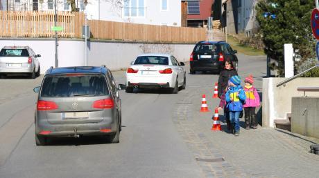 """Halteverbotsschilder und Verkehrswarnkegel sind derzeit während derTestphase """"Sicherer Fußweg an der Hambergstraße"""" in Rehling aufgestellt. Dadurch werden die bislang vor der Bank parkenden Autos auf andere Parkplätze verdrängt und die Fußgänger, vor allem die Schulkinder, können sich dort sicher bewegen."""