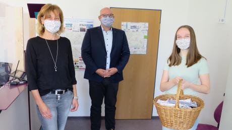 104 Gesichtsmasken spendete die angehende Igenhausener Erzieherin Lena Gütl (rechts). Bürgermeister Xaver Ziegler und EWO-Mitarbeiterin Christine Wolf nahmen die Masken entgegen.