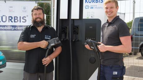 Leopold Kürbis, Geschäftsführer des gleichnamigen Autohauses (links), und Christoph Sturm, Projektmanager E-Mobility bei LEW, nehmen die neue Gleichstrom-Schnellladestation für E-Autos in Betrieb.