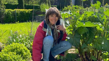 Dr. Maiken Winter mit Kater Smudge in ihrem Gärtchen in Raisting. Das Arbeiten in den Beeten sei wie eine heilsame Therapie, sagt sie. Die essbaren Ringelblumen, die einmal orangefarben blühen, müssen gerade in Zaum gehalten werden.