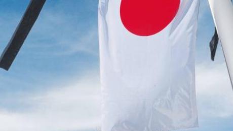 Auf Halbmast gesetzt und mit Trauerflor versehen weht die japanische Fahne in Stadtbergen.