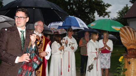 Sorgenvoll blickt Wollmetshofens Pfarrgemeinderatsvorsitzender Alexander Müller zur Kirche, doch Pfarrer Sebastian Nößner und seinen Ministranten kann der Regen nichts anhaben. Auch Kirchenpfleger Peter Luible (3. v. rechts) sucht Schutz unter dem Schirm.