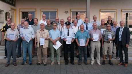 Gemeinsam mit Bürgermeister Bernhard Walter (vordere Reihe rechts) sowie den beiden Vorsitzenden Karl Tretter (hintere Reihe rechts) und Vize Erwin Glenk (mittlere Reihe links) stellten sich 22 Gründungsmitglieder des TSV Zusamzell-Hegnenbach beim Festabend zu einem Erinnerungsfoto.