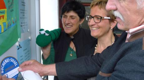 Bürgermeister Bernhard Walter bringt das Gütesiegel in Gold im Schaukasten der Violauer Bücherei an. Leiterin Ruth Schmid (Mitte) und Monika Klaus (mit dem Maskottchen) vom Büchereiteam assistieren ihm.