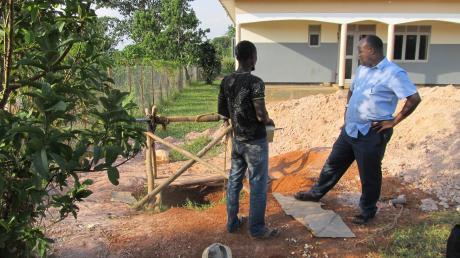 Brunnenbau in Uganda: Pfarrer Denis Lwegaba (rechts) und ein Vertreter der ausführenden Firma vor der erstaunlich engen Brunnen-Baustelle. Der Brunnen wurde völlig ohne Einsatz von Baumaschinen von Hand ausgehoben. Auf Wasser stieß man erst in über 60 Metern Tiefe.