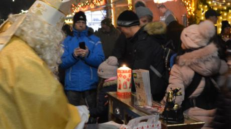 Der Nikolaus teilt vor seinem Postamt Karten an die Kinder aus, die ihm schreiben möchten.