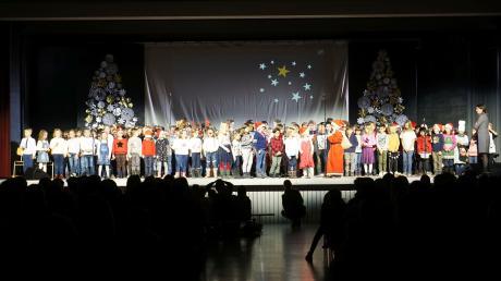"""Da sie sich nicht einigen konnten, sangen die Erst-, Zweit- und Drittklässler eben ein """"Weihnachtslieder-Medley"""". Rektorin Elisabeth Kick (rechts außen) begleitete sie dabei."""