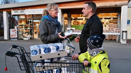 Landwirt Andreas Kraus aus Deubach verteilt bei Edeka Schmid in Steppach seinen Joghurt, um auf die Bedeutung regionaler Nahversorgung und die Probleme der Landwirte aufmerksam zu machen. Mit im Bild sein Neffe Bastian, der beim Verteilen hilft, und Kundin Monika Heigl.