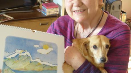 Annette Bartusch-Goger freut sich wieder über einen Kunstkalender 2020, auf dem auch Hund Sina immer wieder abgebildet ist. Das Motiv des Neusässer Rathauses soll zukünftig Geschenktassen der Stadt Neusäß schmücken.
