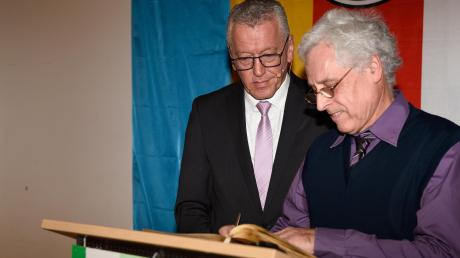Georg Knöpfle (rechts) trägt sich unter den Augen von Bürgermeister Anton Gleich ins Goldene Buch der Gemeinde Bonstetten ein.