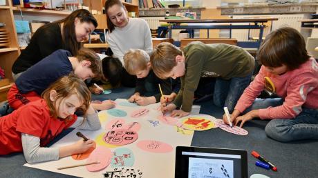 Lehramtsanwärter gestalten in Dinkelscherben in der Montessori-Schule eine besondere Unterrichtsstunde. Hinten (von links): Leonie Brenner und Natalie Heiler erstellen mit den Kindern ein Plakat zum Thema Cyber-Mobbing.