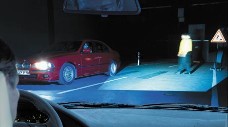 Ein junger Mann läuft in der Nacht einfach über die Straße, ohne auf den Verkehr zu achten.
