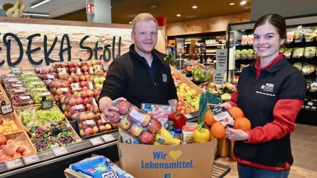 Filialleiter Stefan Langhammer und Annkathrin Ronecker packen die Lebensmittelbestellungen in Kisten, die dann per Taxi ausgeliefert werden.
