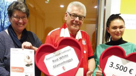 Rudi Tausend (Mitte) überbringt im Namen der Red-White-Glammhogga die Zusage, dass der Bayern-Fanclub aus Gablingen die Finanzierung von 100 Typisierungen übernimmt.
