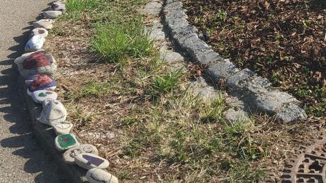 Bemalte Steine formen sich an der großen Kreuzung in Rommelsried zu einer lustigen Steinschlange. Kunstwerke wie dieses sollen in der Corona-Krise Mut machen.