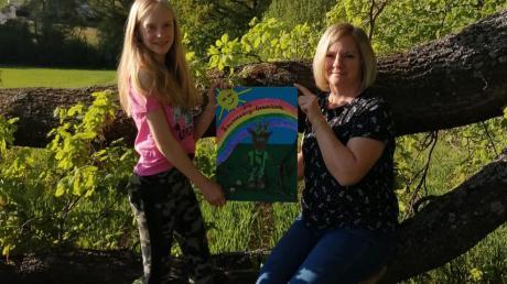 Melissa (links) und Carmen Memminger zeigen das Cover ihrer Baumzwerg-Geschichte, die zu einem richtigen Buch werden soll.