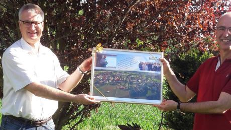 """Stefan Vogg (links) überreicht Richard Hegele (rechts) zum Abschied ein Bild seines Ortsteils Wörleschwang mit den Grüßen der neuen Wählergruppierung """"Bürgerliste Zusmarshausen""""."""