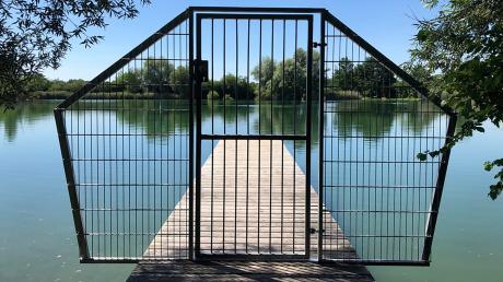 Der Badesteg am Weiher in Thierhaupten ist durch ein Tor versperrt. Es wird nur geöffnet, wenn die Wasserwacht da ist. Im Jahr 2019 war es zu einem tödlichen Badeunfall gekommen.