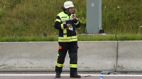 Ein Feuerwehrmann koordiniert am Rande des Unfalls auf der A8 die Einsatzkräfte. Eine Person starb, vier wurden schwer verletzt. Ein Auto wurde entzwei gerissen und landete auf der Gegenfahrbahn.