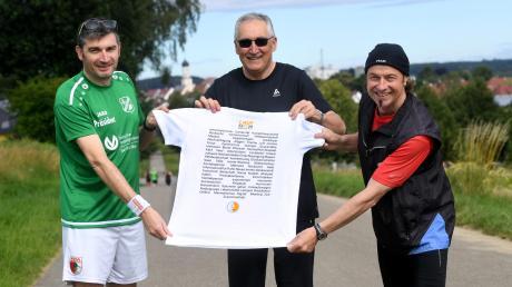 TSV-Vorsitzender Gerhard Biber, stellvertretender Landrat Hubert Kraus und Zusmarshausen Bürgermeister Bernhard Uhl präsentieren das T-Shirts, das Unterstützer erhalten.