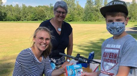 Luis ließ sich von Valentina Brüning eine Widmung in sein Buch schreiben. Mit ihm freuen sich die Autorin und Elisabeth Wagner-Engert, die Leiterin der Pfarrbücherei Ellgau und Organisatorin der Lesung auf dem Sportplatz.